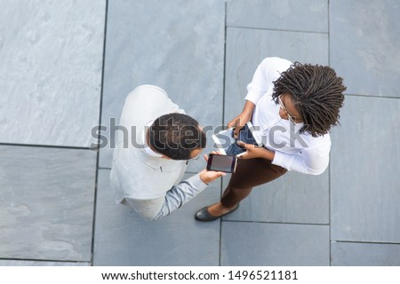 Business colleagues with gadgets meeting near office and discussing project. Top view of business man and woman standing outside, talking and using tablet and mobile phone. Communication concept #1496521181