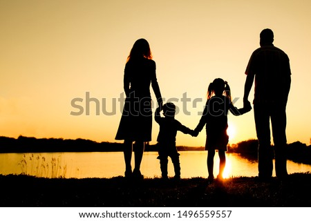 silhouette family, including his father, mother and two children in the hands of #1496559557