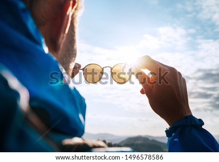 Backpacker man looking at bright sun through polarized sunglasses  enjoying mountain landscape. Eye & Vision Care human health concept image. Royalty-Free Stock Photo #1496578586