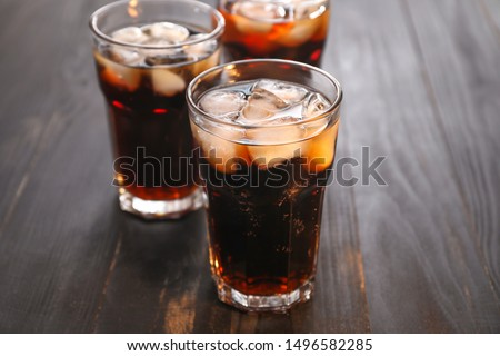 Glasses of cold cola on wooden table #1496582285