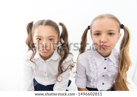Unhappy cuties. Unhappy little schoolchildren isolated on white. Adorable small girls with unhappy emotions looking in camera. Unhappy because of school starts. #1496602811