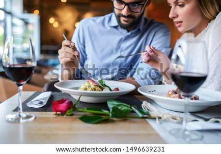 Romantic couple enjoying lunch in the restaurant, eating paste and drinking red wine. Lifestyle, love, relationships, food concept #1496639231