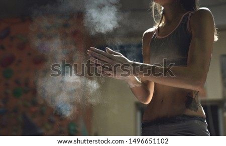 closeup view of woman climber is chalking and clapping hands with white chalk powder before climb in indoor climbing gym. woman getting ready to climbing. exercising and training in climbing gym. #1496651102