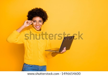 Photo of charming cute black curly attractive girlfriend holding her laptop and spectacles searching for something getting likes wearing jeans denim yellow pullover isolated vivid color background