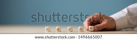Wide view image of hand of a businessman placing wooden cubes with contact, communication and location icons in a row. Royalty-Free Stock Photo #1496665007