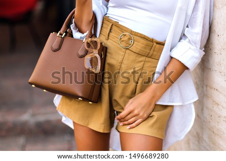 Street style fashion details, tanned woman wearing linen shorts, white shirt, brown leather bag and clear beige sunglasses, modern classic summer chic outfit, warm colors. #1496689280