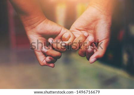 Hand to pinky swear,Happy couple or friendship holding hands together forever love concept. #1496716679