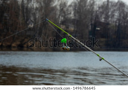 fishing bell hanging on a fishing line, summer photo on nature, blurred background, in the background a lake #1496786645