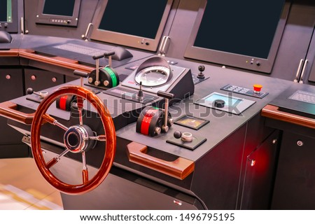 Captains bridge. Boat control panel with steering wheel on the captain bridge. Wheelhouse on a motor yacht. The place of the captain of the ship. Electronics on a modern ship. Boat management courses. #1496795195