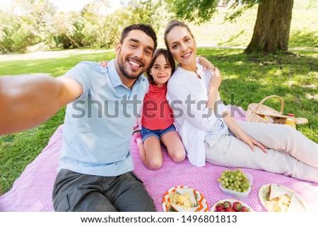 family, leisure and technology concept - happy mother, father and daughter having picnic and taking selfie at summer park