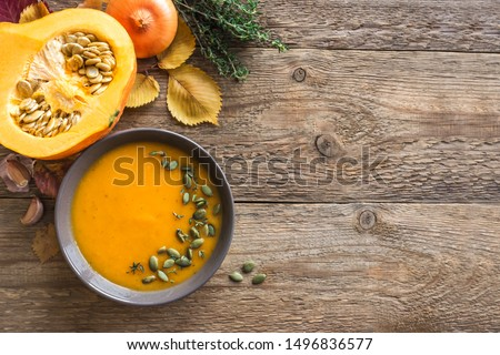 Pumpkin soup and organic pumpkins on wooden background, copy space. Seasonal autumn food - Spicy pumpkin soup with thyme and pumpkin seeds. #1496836577