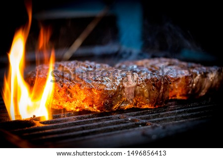 Barbecue ancho steak. Grilled ancho steak on barbecue grill with fire. BBQ Steak ancho meat steak #1496856413