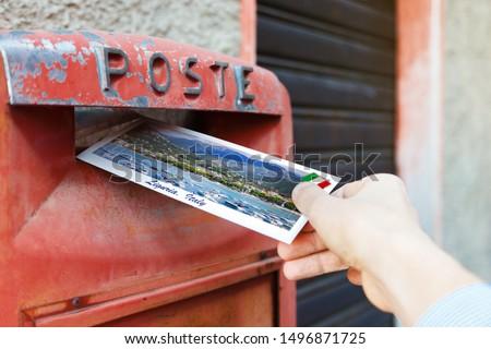 Male hand sends a postcard to a red mailbox in Liguria region, Italy. The postcard shows a Liguria coast, Sestri Levante city