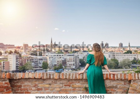 Beautiful attractive red hair woman in sensual green dress posing in locations of the city.  #1496909483