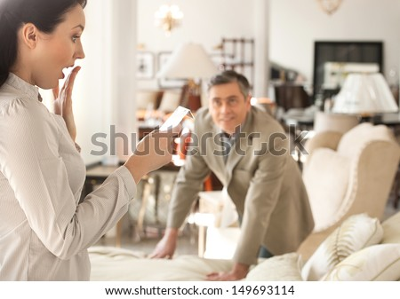 Shocked with a price. Shocked middle-aged woman holding a price while standing near her husband at the furniture store #149693114