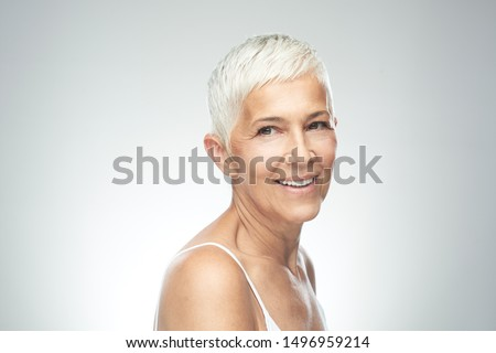 Beautiful smiling senior woman with short gray hair posing in front of gray background. Beauty photography. #1496959214