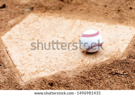 Baseball laying on a worn home plate or base Royalty-Free Stock Photo #1496981435
