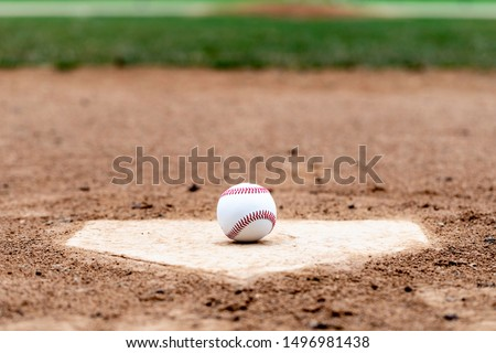 Baseball laying on a worn home plate or base #1496981438