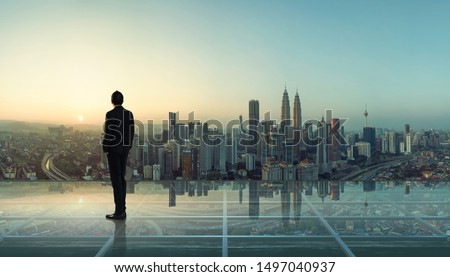 Businessman standing at transparent glass floor on rooftop with city skyline, success and thinking concept  . #1497040937
