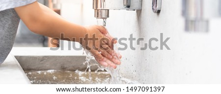 Banner of a student boy wash hands at the outdoor wash basin in the school. Preventing Contagious diseases, Plague. Kids health, Hygiene, Flu, H5N1 influenza, Saving water, Covid-19, New normal. Royalty-Free Stock Photo #1497091397