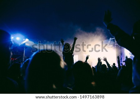 Silhouettes of raised hands on the concert in the night. Little girl with the hands up is sitting on the neck. The crowd of people at the open air music festival. Music background. #1497163898