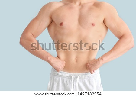 Handsome muscular man on color background. Weight loss concept #1497182954
