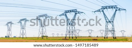 Panoramic view of a row of electricity pylons next to a road in the french countryside with dozens of other pylons in the distance under a clear blue sky. #1497185489