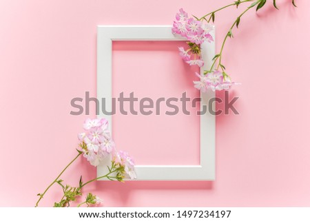 White wooden picture frame and flowers on pink background with copy space. Creative Top view Flat lay Mock up Template for invitstion, greeting card.