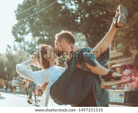 Cheerful cheerful hipster couple in love kissing in a city street. The romantic concept of lovers. love story #1497251510