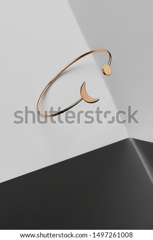 Subject shot of a golden open bracelet made of thin wire decorated with the half-moon and the little disk by the ends. The bracelet is isolated on the surface with geometric details.  #1497261008