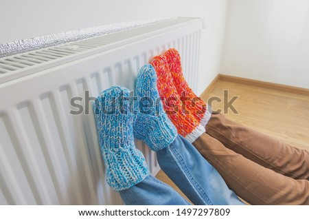 Family in warm knitted woolen socks near a home heater in cold winter time. The symbolic image of the heating season at home. Part of body, selective focus. #1497297809