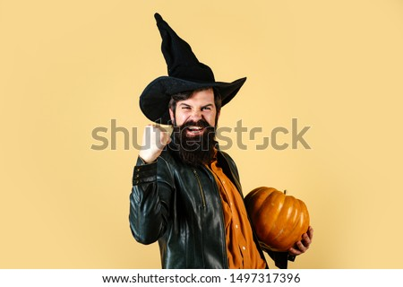 Handsome Halloween man with pumpkin in hand. Devil man. Design for Halloween banner. Young man with witch hat ready to Halloween party. Happy Halloween Stickers #1497317396