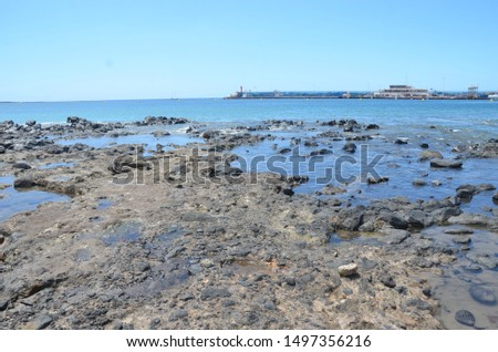 Some rocks in a Tenerife's beach full of other volcanic rocks and stones. #1497356216