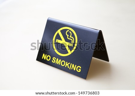 A black no smoking sign displayed on a white table
