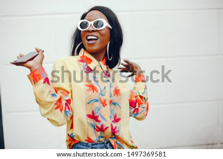 A beautiful and stylish black girl with long dark hair dressed in a yellow shirt and with sunglasses standing near wall in a summer city and use the phone #1497369581