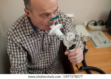 Senior hispanic man man testing breathing function by spirometry. Diagnosis of respiratory function in pulmonary disease #1497378077