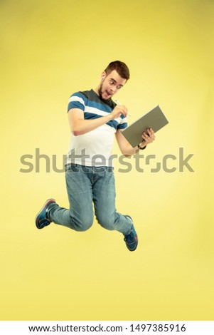 Full length portrait of happy jumping man with gadgets on yellow background. Modern tech, freedom of choices concept, emotions concept. Using graphic tablet for work and art in flight. #1497385916