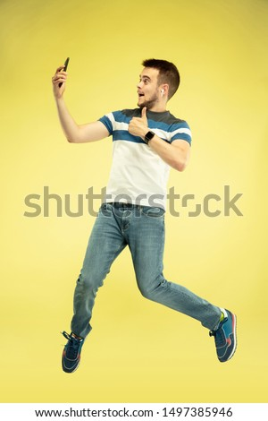 Communication. Full length portrait of happy jumping man with gadgets on yellow background. Modern tech, freedom of choices concept, emotions concept. Using smartphone for selfie or videocall in #1497385946