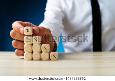 Businessman making a stack of wooden dices assembling an arrow shooting upwards in a conceptual image. Over navy blue background. #1497388952