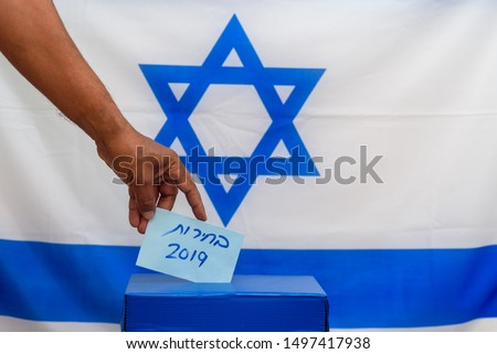 Election in Israel - voting at the ballot box. The hand of man putting vote in the ballot box. Israeli Flag on background. Hebrew text Elections 2019. #1497417938