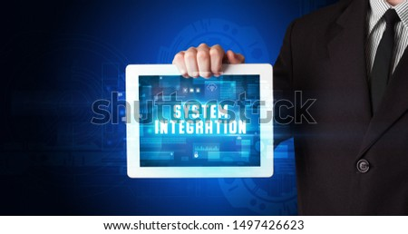 Young business person working on tablet and shows the digital sign: SYSTEM INTEGRATION #1497426623