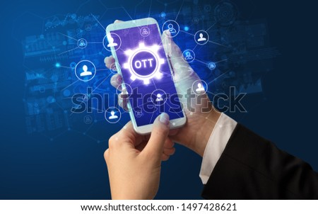 Female hand holding smartphone with OTT abbreviation, modern technology concept #1497428621