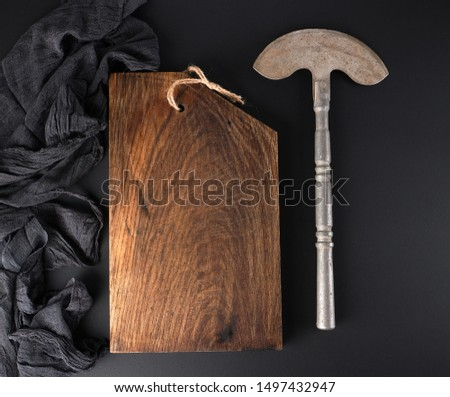 empty brown cutting board and old iron hatchet for cutting meat or vegetables on black board, top view #1497432947