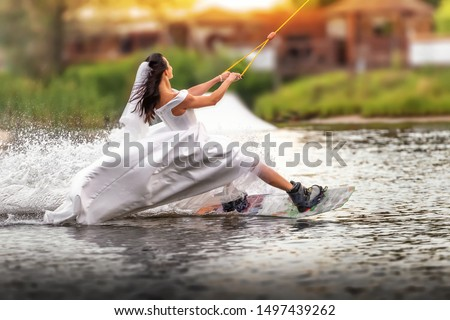 A young girl in a wedding dress riding on a wakeboard on the lake. Extreme bride. Unusual bride. An extraordinary bride. #1497439262