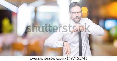 Young handsome business man wearing glasses over isolated background In hurry pointing to watch time, impatience, upset and angry for deadline delay #1497451748