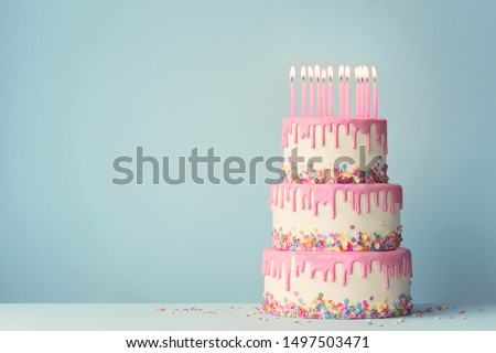 Tiered birthday cake with drip frosting and twelve candles #1497503471