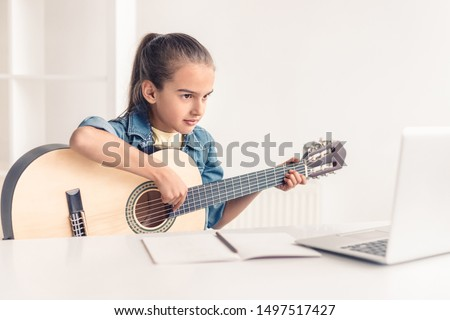 Focused little kid playing acoustic guitar and watching online course on laptop while practicing at home Royalty-Free Stock Photo #1497517427