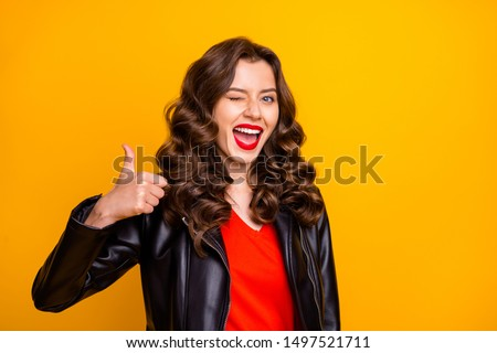 Close up photo of lady with red lips raising thumb up and winking eye wear leather jacket isolated yellow color background #1497521711