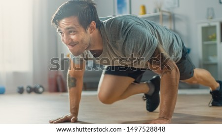 Muscular Athletic Fit Man in T-shirt and Shorts is Doing Mountain Climber Exercises While Using a Stopwatch on His Phone. He is Training at Home in His Bright Living Room with Minimalistic Interior. #1497528848