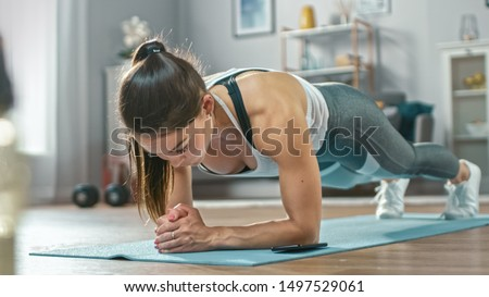 Strong Beautiful Fitness Girl in Athletic Workout Clothes is Doing a Plank Exercise While Using a Stopwatch on Her Phone. She is Training at Home in Her Living Room with Cozy Interior. #1497529061